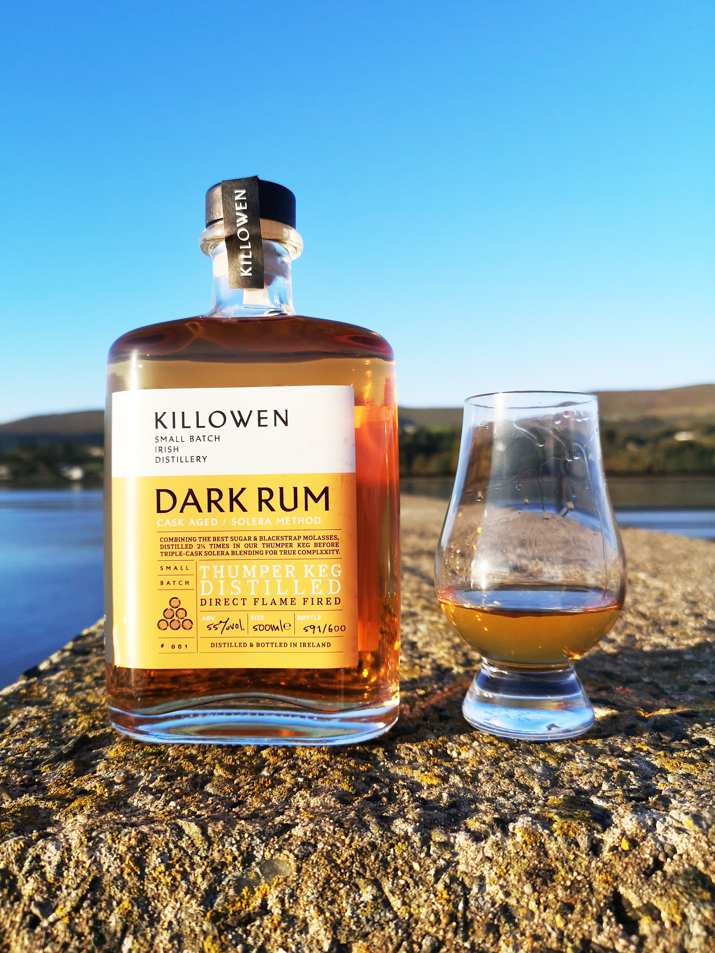 A small bottle of rum sitting on a sea rock in the sun